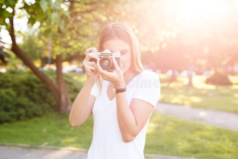 Den gulliga flickan på solig dag i parkering som tar foto med motsvarighet, kom arkivbild