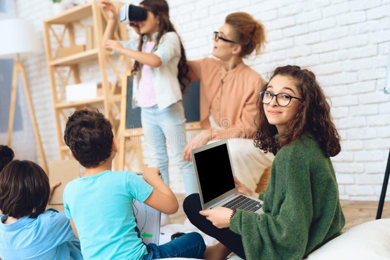 Den gulliga flickan ser in i virtuell verklighetexponeringsglas på klassrumet av grundskolan royaltyfri foto
