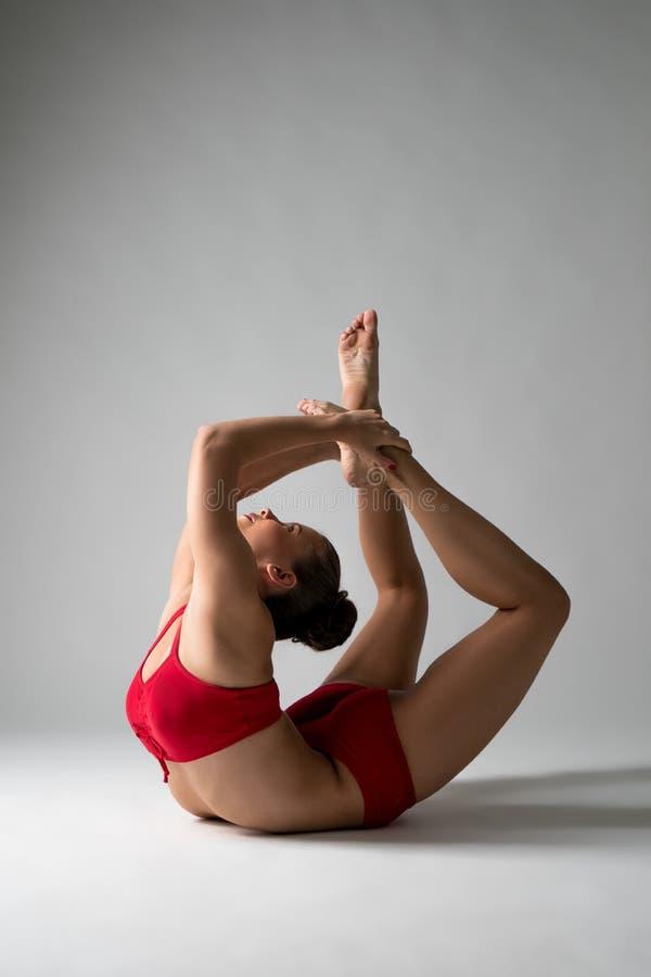 Den gulliga flickan utför den svåra gymnastiska beståndsdelen royaltyfri foto