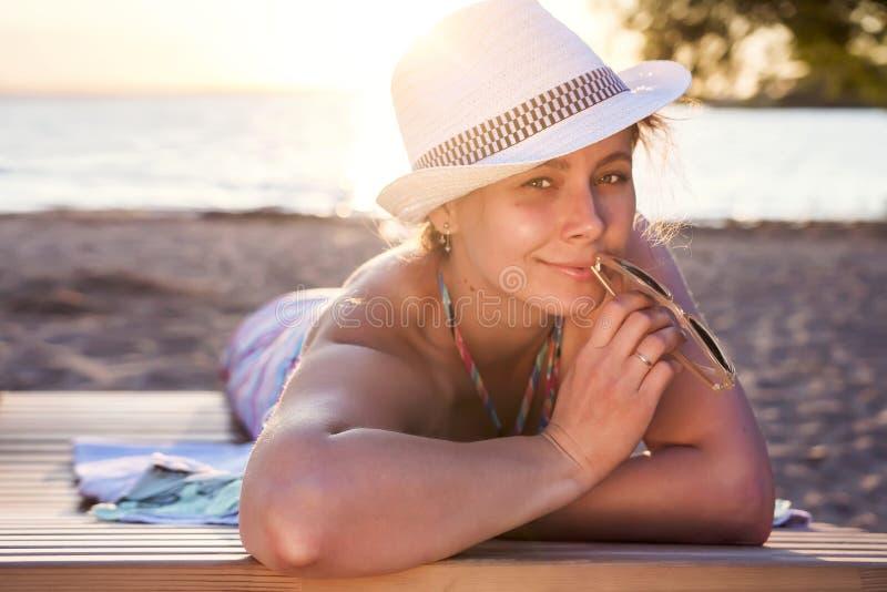 Den gulliga härliga attraktiva brunbrända damen i hatt ligger på deckchair på havsstranden på solnedgången på varm sommarafton Nä royaltyfri fotografi