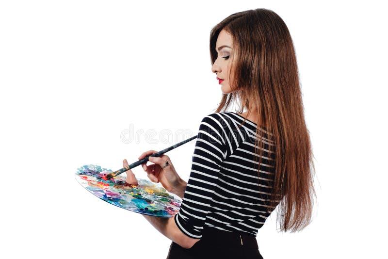 Den gulliga härliga flickakonstnären som rymmer en palett och en borste i processen, drar inspiration Vitbakgrund som isoleras royaltyfri fotografi
