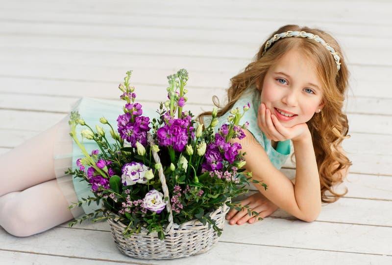 Den gulliga h?rliga lilla flickan med blont h?r ligger i en ljus studio bredvid en korg med nya blommor royaltyfria foton