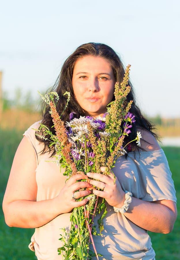 Den gulliga härliga ståenden för den unga kvinnan med fältet blommar under sommarsolnedgång arkivbilder