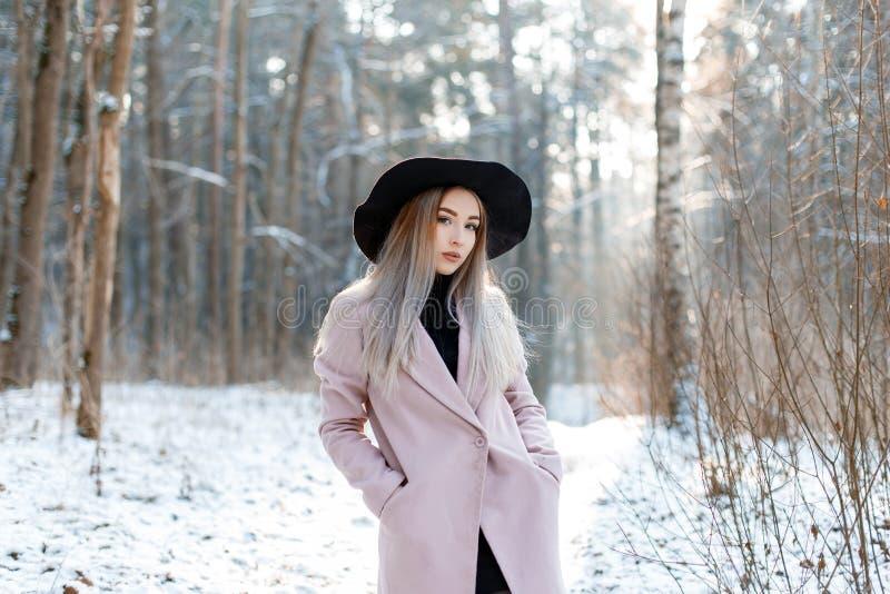 Den gulliga härliga unga kvinnan med blont hår i en chic svart hatt för tappning i ett rosa elegant lag som poserar i en vinter,  arkivfoto