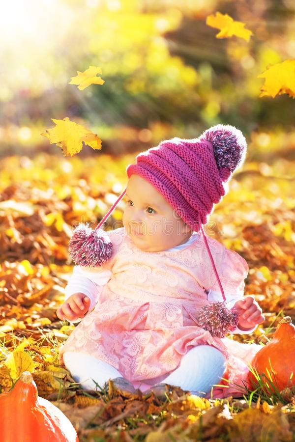 Den gulliga hösten behandla som ett barn flickan i guld- mjukt ljus arkivbilder
