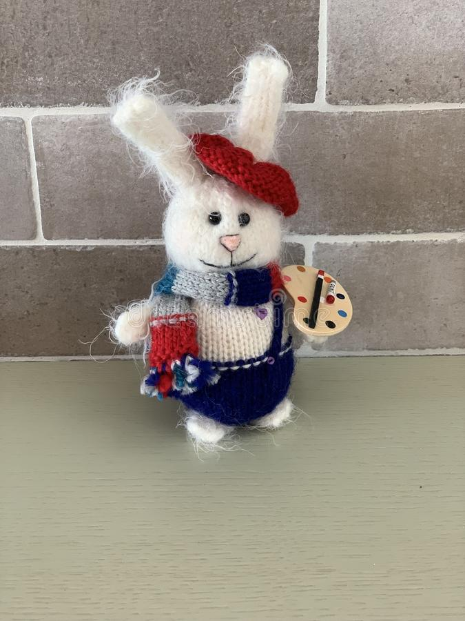Den gulliga handen - gjorde hare- eller kaninkonstnärleksaken som stacks med målarfärger och halsduken arkivfoto