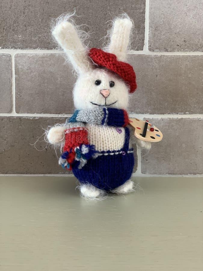 Den gulliga handen - gjorde hare- eller kaninkonstnärleksaken som stacks med målarfärger och halsduken royaltyfri bild