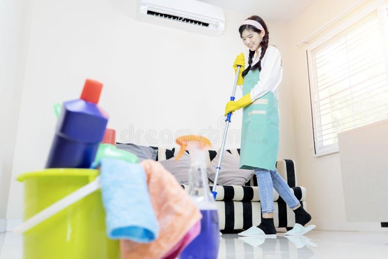 Den gulliga hemmafrun moppar golvet med en golvmopp royaltyfri fotografi