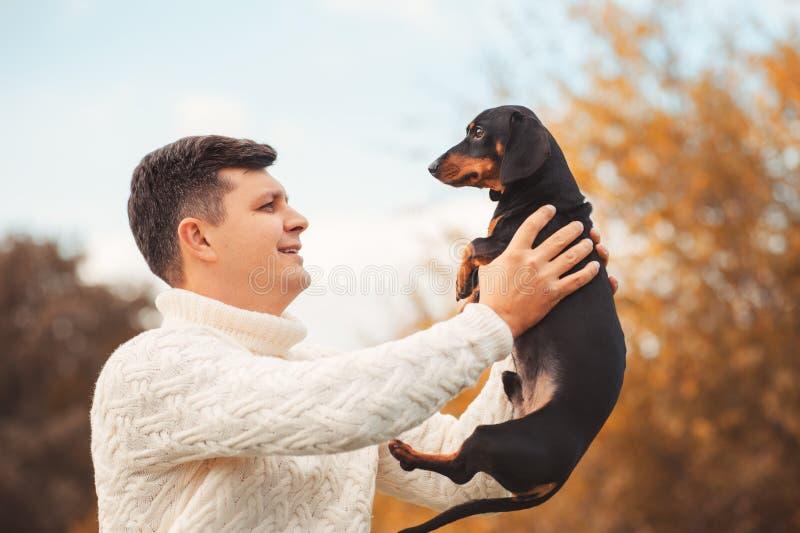 Den gulliga hunden och hans unga stiliga man för ägare har gyckel i parkera, befruktningdjur, husdjur royaltyfri foto