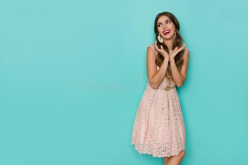 Den gulliga kvinnan i beiga snör åt Mini Dress Is Holding Head, i händer och att skratta royaltyfri bild