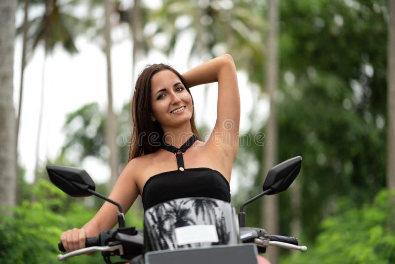 Den gulliga kvinnan ler och rätar ut hennes hår som sitter bak hjulet av en sparkcykel royaltyfria foton