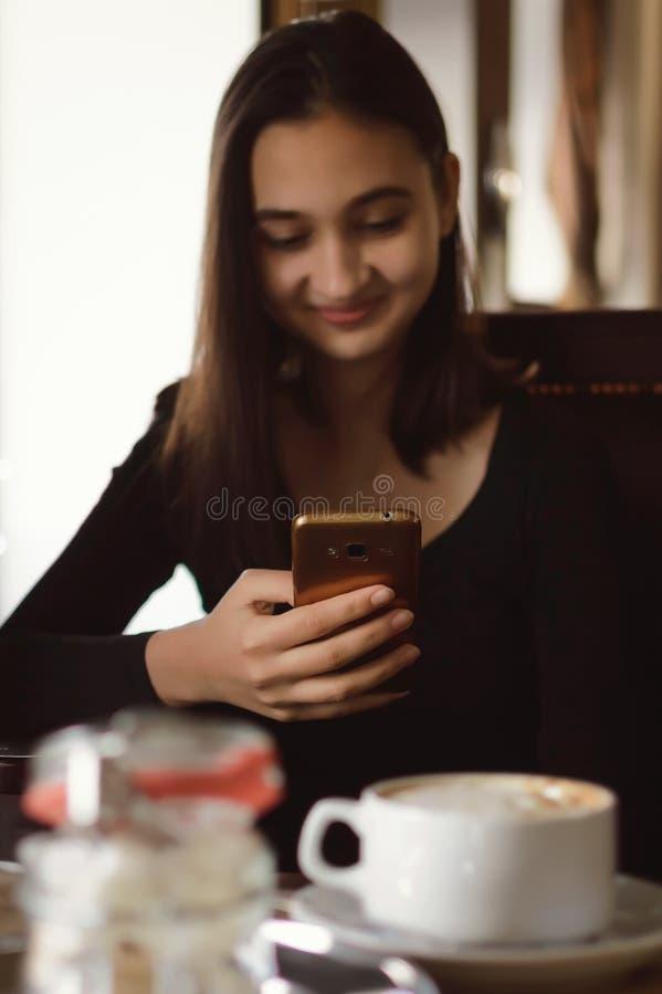 Den gulliga långhåriga flickan sitter i en kafeteria och använder internet i en mobiltelefon ung gullig kvinna som använder telef arkivbilder