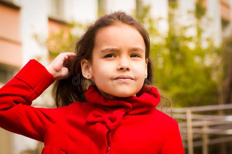 Den gulliga le flickan i ett rött lag och stoppar hennes hår fotografering för bildbyråer
