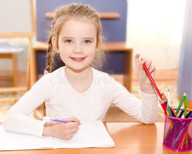 Den gulliga le lilla flickan skriver på skrivbordet royaltyfria foton
