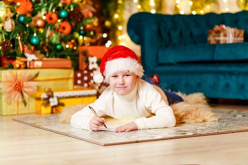 Den gulliga le pojken i jultomten röda lock skrivar ett brev till Santa Claus för jul royaltyfri foto