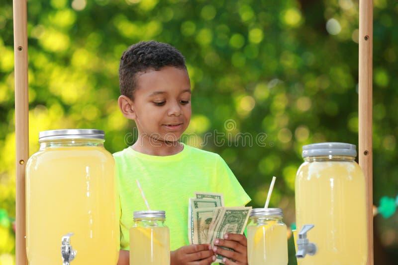 Den gulliga lilla afrikansk amerikanpojken med pengar på lemonadställningen parkerar in Uppfriskande drink f?r sommar arkivbilder