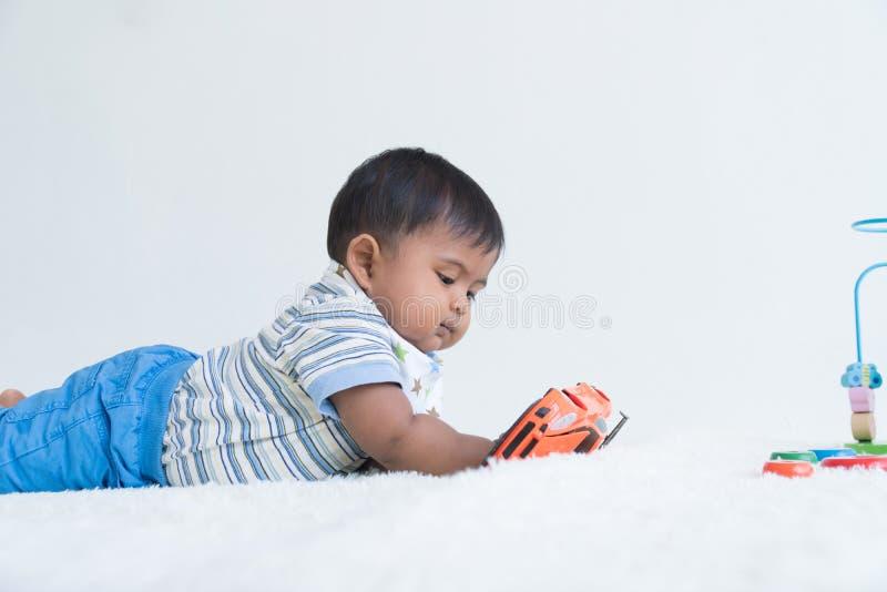 Den gulliga lilla asiatet behandla som ett barn att ligga på den mjuka filt- och lekleksakbilen royaltyfria bilder
