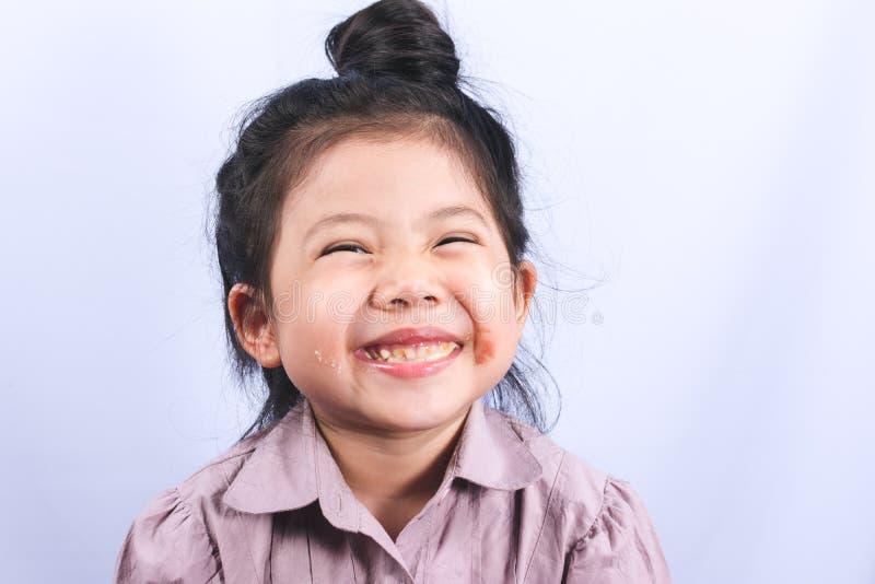 Den gulliga lilla asiatiska flickan är den slarviga munnen arkivbild