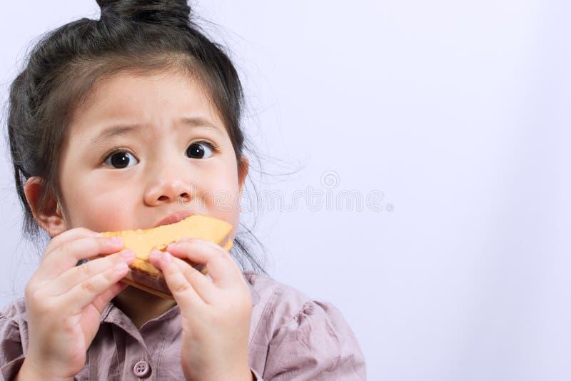 Den gulliga lilla asiatiska flickan äter royaltyfri foto