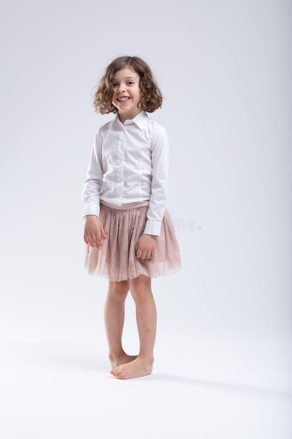 Den gulliga lilla barfota flickaanseendeduvan toed royaltyfri bild