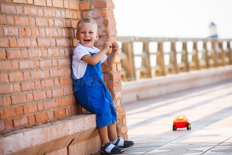 Den gulliga lilla blonda pojken spelar royaltyfri foto