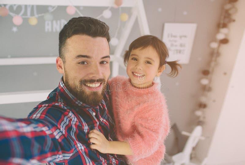 Den gulliga lilla dottern och hennes stiliga unga farsa spelar tillsammans i rum för barn` s Pappan och barnet spenderar tid arkivfoton