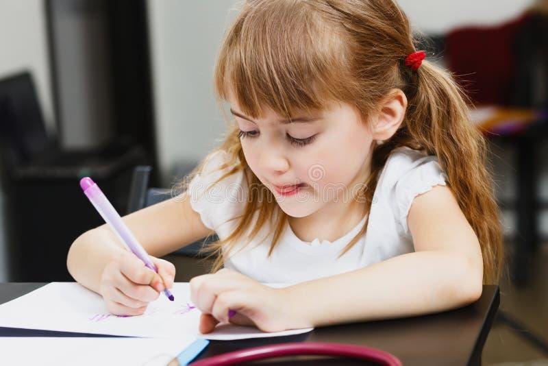 Den gulliga lilla förskolebarnflickan drar med färgrika tuschpennor fotografering för bildbyråer