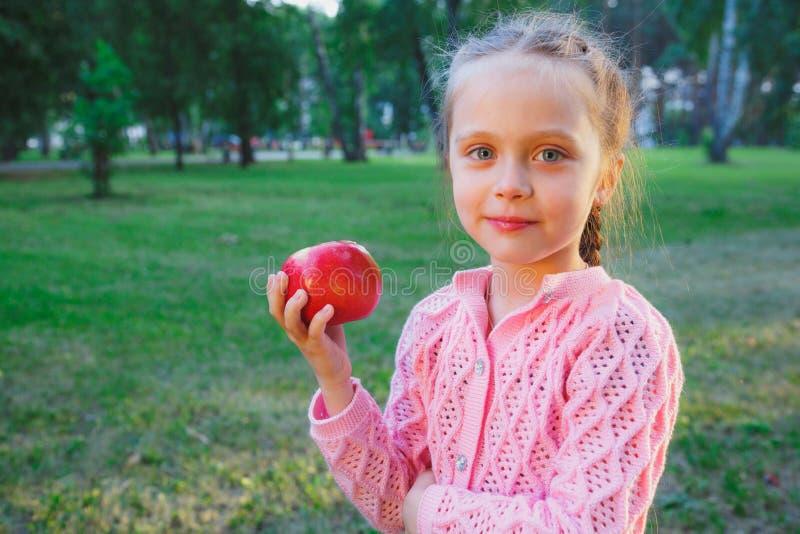 Den gulliga lilla flickan äter rött - det läckra äpplet arkivfoton