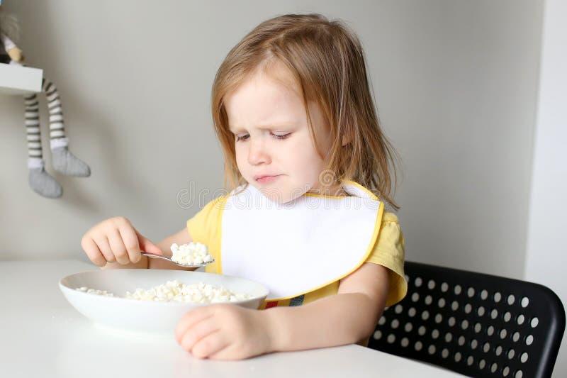 Den gulliga lilla flickan önskar inte att äta kvarken på kök royaltyfria foton
