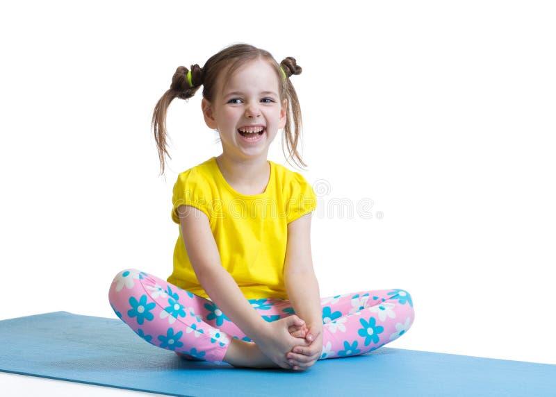 Den gulliga lilla flickan går in för sportar på en vit bakgrund arkivfoto