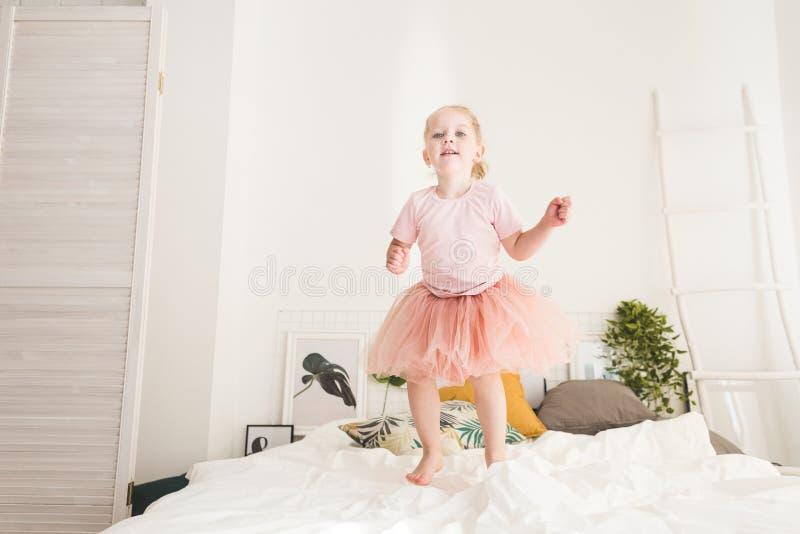 Den gulliga lilla flickan har gyckel p? s?ngen hemma royaltyfria foton