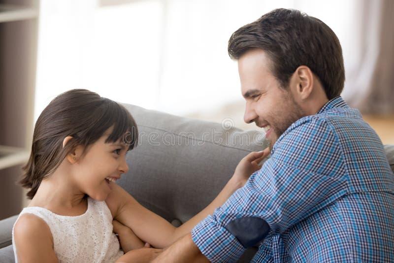 Den gulliga lilla flickan har gyckel som spelar med den unga farsan arkivbilder