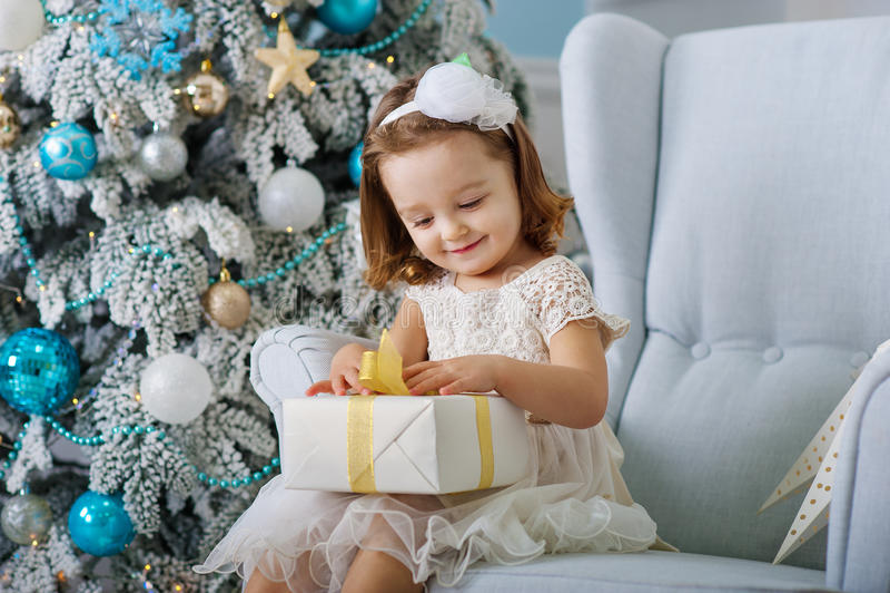 Den gulliga lilla flickan i bklomklänningsammanträde i en stol och öppnar asken med gåva för bakgrundsjulgranblått arkivfoto