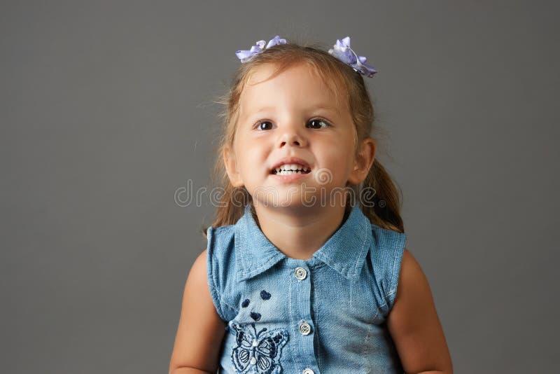Den gulliga lilla flickan i blått klär att le och uppvisning av hennes tänder fotografering för bildbyråer