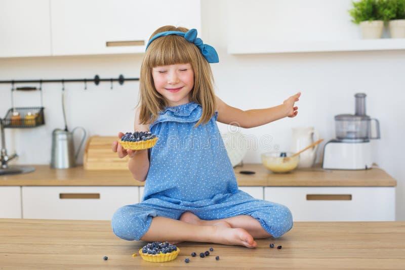 Den gulliga lilla flickan i blåttklänning sitter på en tabell med en kaka i en hand och stängda ögon royaltyfria bilder