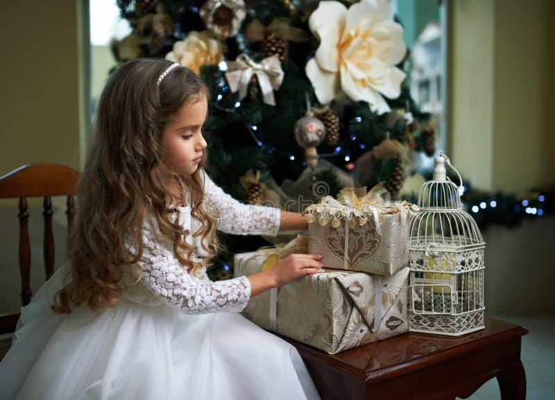 Den gulliga lilla flickan i den vita klänningen ser gåvor arkivfoton
