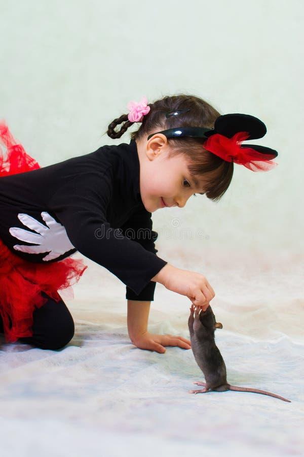 Den gulliga lilla flickan i en björndräkt med öron rymmer en hand tjaller royaltyfria foton