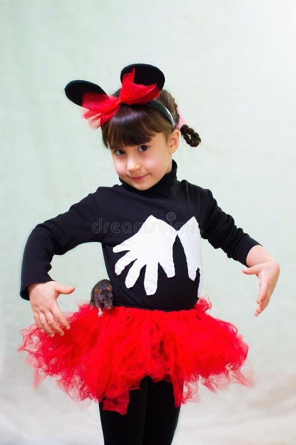 Den gulliga lilla flickan i en björndräkt med öron rymmer en hand tjaller royaltyfria bilder