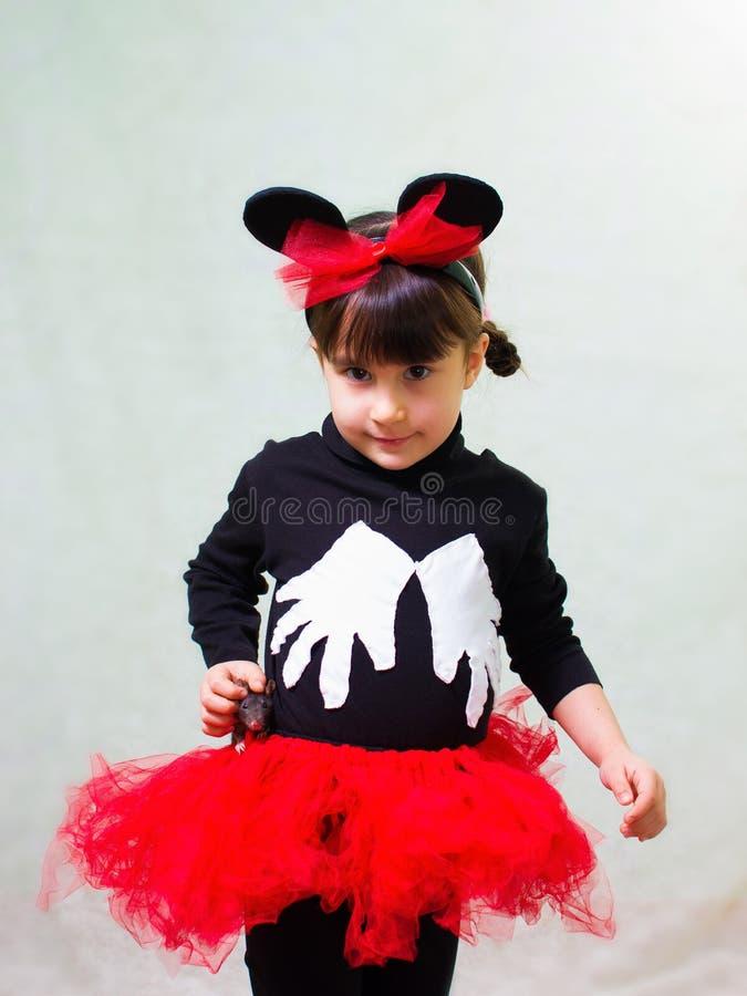 Den gulliga lilla flickan i en björndräkt med öron rymmer en hand tjaller fotografering för bildbyråer