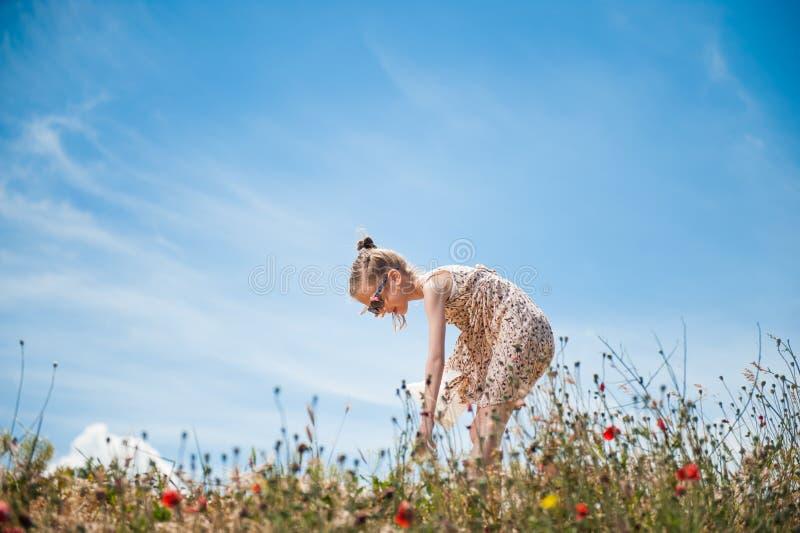 Den gulliga lilla flickan i klänningen som är nedböjd till hackan, blommar i fält royaltyfria foton
