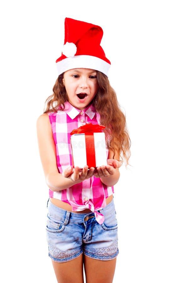 Den gulliga lilla flickan i den santa hatten rymmer en gåva i hennes hand och öppnar royaltyfri foto