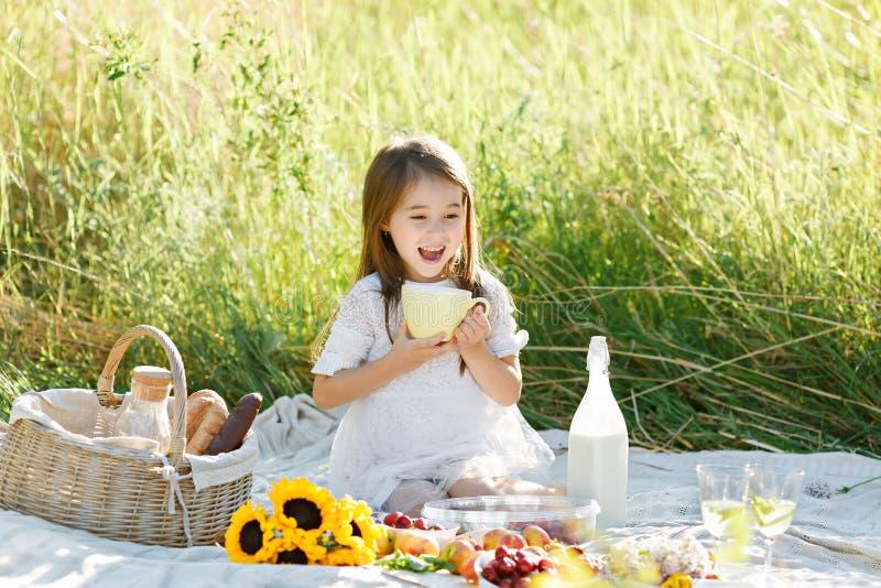 Den gulliga lilla flickan i den vita kläderna som sitter på dricka för fält, mjölkar och att le royaltyfri fotografi