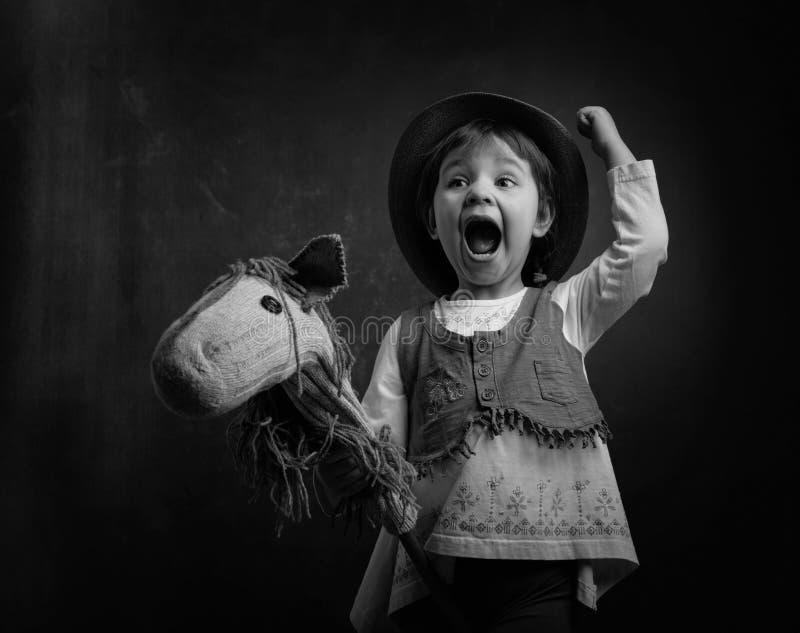 Den gulliga lilla flickan klädde som en cowboy som spelar med ett hemlagat H royaltyfri foto