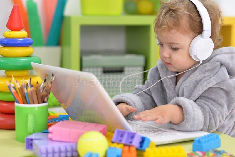 Den gulliga lilla flickan lyssnar till musik royaltyfria bilder