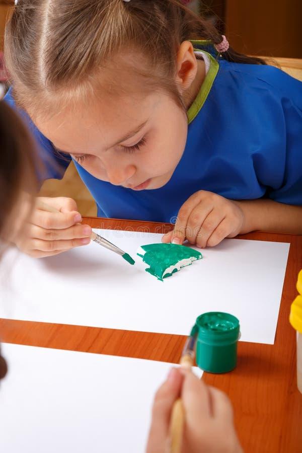Den gulliga lilla flickan målar royaltyfri foto