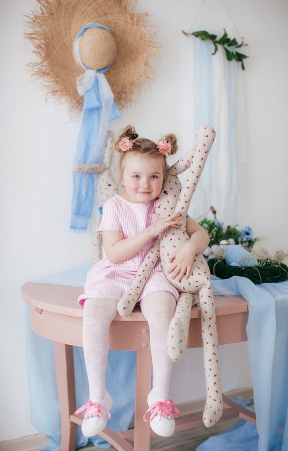 Den gulliga lilla flickan med en kaninkanin har en p?sk royaltyfri fotografi