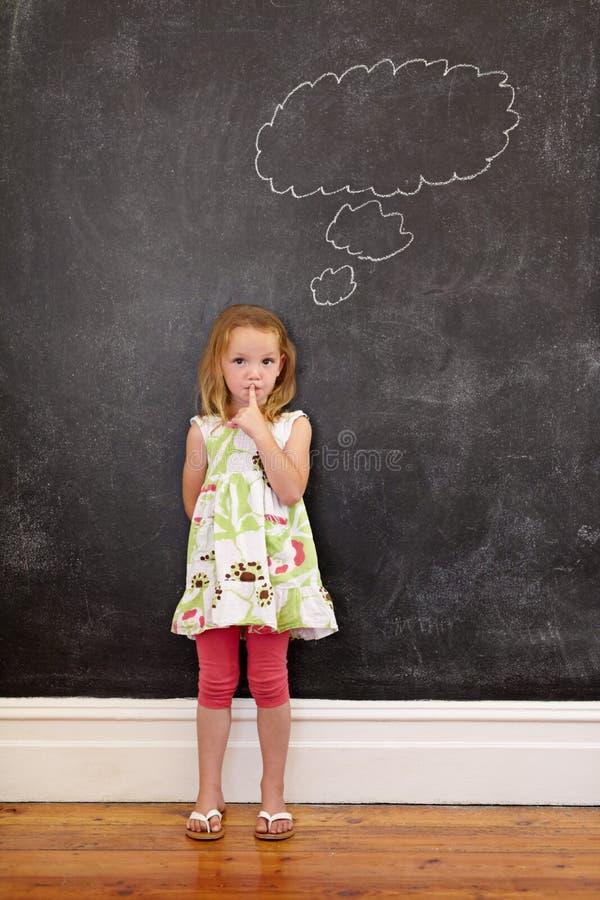 Den gulliga lilla flickan med hennes finger på kanter och en tanke bubblar royaltyfri foto