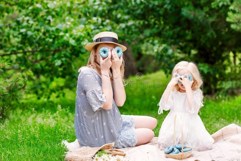 Den gulliga lilla flickan med hennes gravida moder har en picknick, lycka?gonblick i familjlivsstil royaltyfria foton