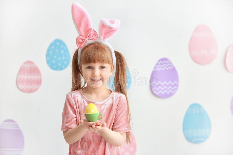 Den gulliga lilla flickan med kaninen gå i ax det hållande ljusa påskägget arkivfoton