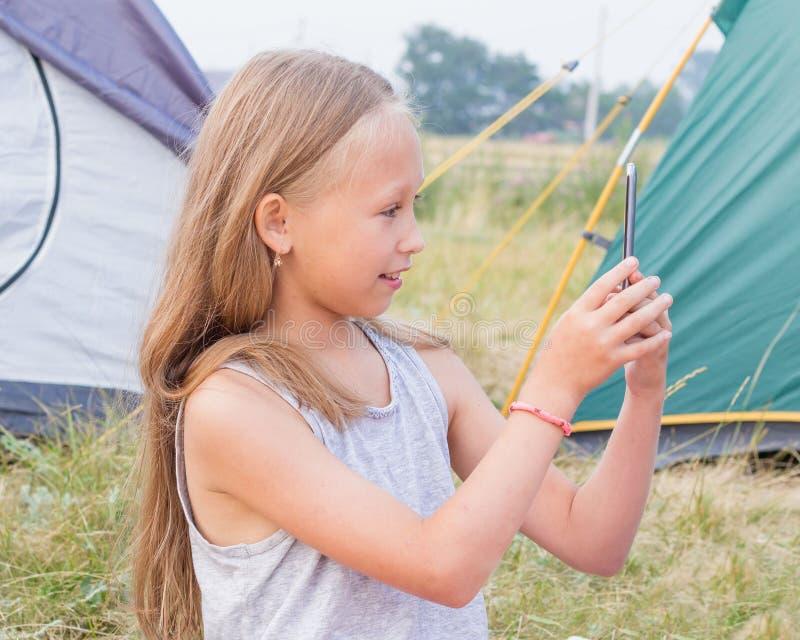 Den gulliga lilla flickan med långt blont hår tar en bild på en smartphone på en bakgrund av tält arkivbild